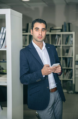 Handsome businessman holding smartphone leaning on a bookcase in headquarters Business Busy Company Man Suit Working Business Finance And Industry Businessman Caucasian Chairman Chief Concentration Device Executive  Headquarters Jacket Job Male One Person Portrait Serious Smart Phone Sucess Technology Vertical