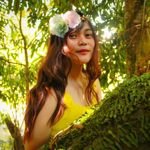 Portrait of beautiful young woman by tree