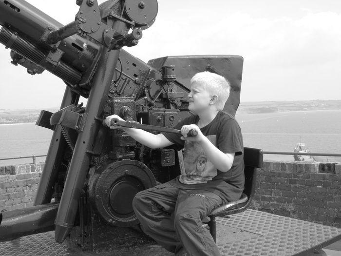 Boy Holding Cannon Against Sea