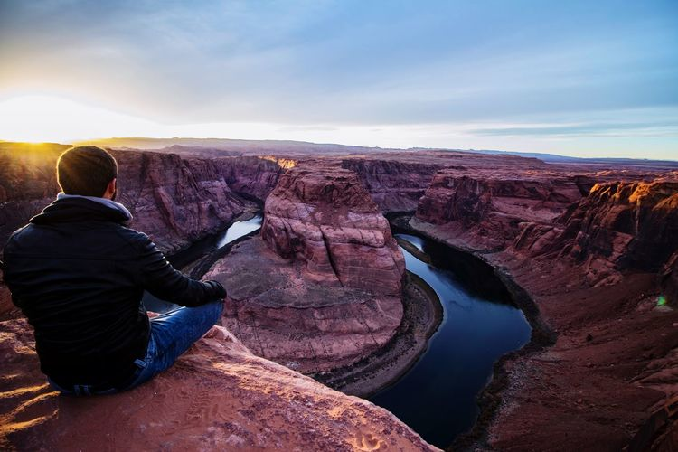 Rear view of man sitting at horseshoe bend against sky