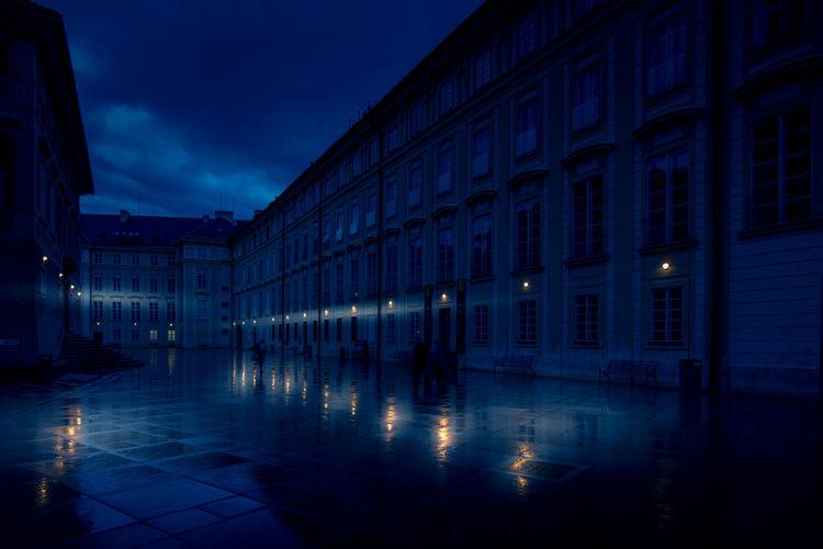 Illuminated buildings by wet street against sky at dusk