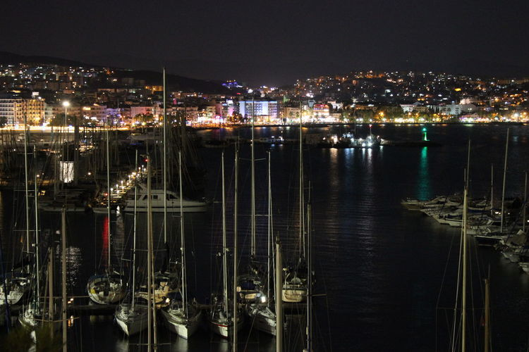 High angle view of illuminated harbor against buildings at night