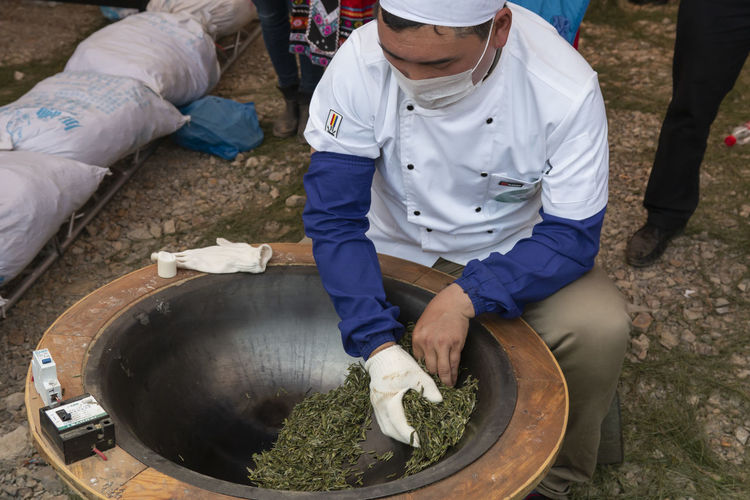 Yiliang, China - March 23, 2019: Chinese man drying green tea in a pan. This process it's also called tea frying Yiliang Kunming, China Tea Tea Leaves Tea Harvesting Yi Minority Ethnic Group China ASIA Tea Garden Tea Production Tea Processing Puer Tea Oolong Tea