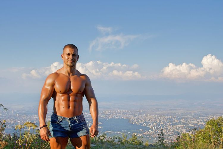 Portrait of shirtless muscular man standing on mountain against sky