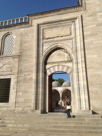 Entering the courtyard of Sulemaniye mosque Arch Architecture Building Exterior Built Structure Clear Sky Cultures History Lone Figure Ottoman Architecture Outdoors People Sinan Sulemaniye Mosque Travel Destinations