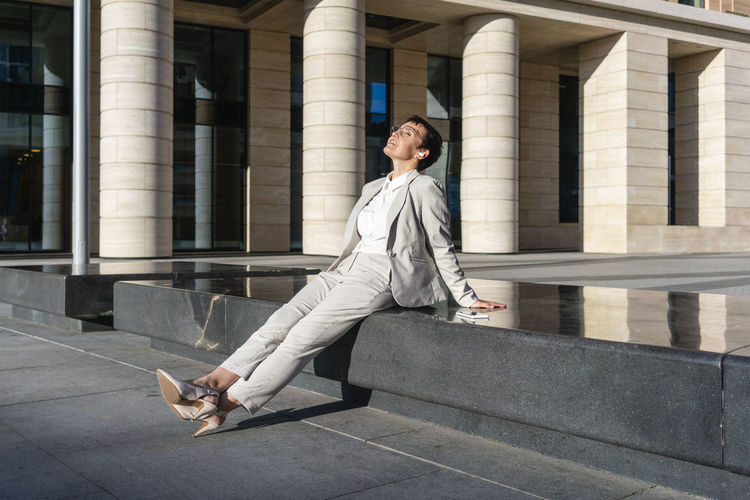 Full length of woman sitting on building in city