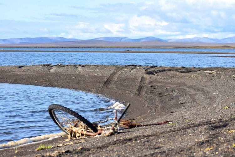 Washed up bike Metal Old Rust Bike Water Sky Cloud - Sky Scenics - Nature Beauty In Nature Mountain Tranquility Nature Day Tranquil Scene Land Beach No People Sea Non-urban Scene Sunlight Outdoors Environment