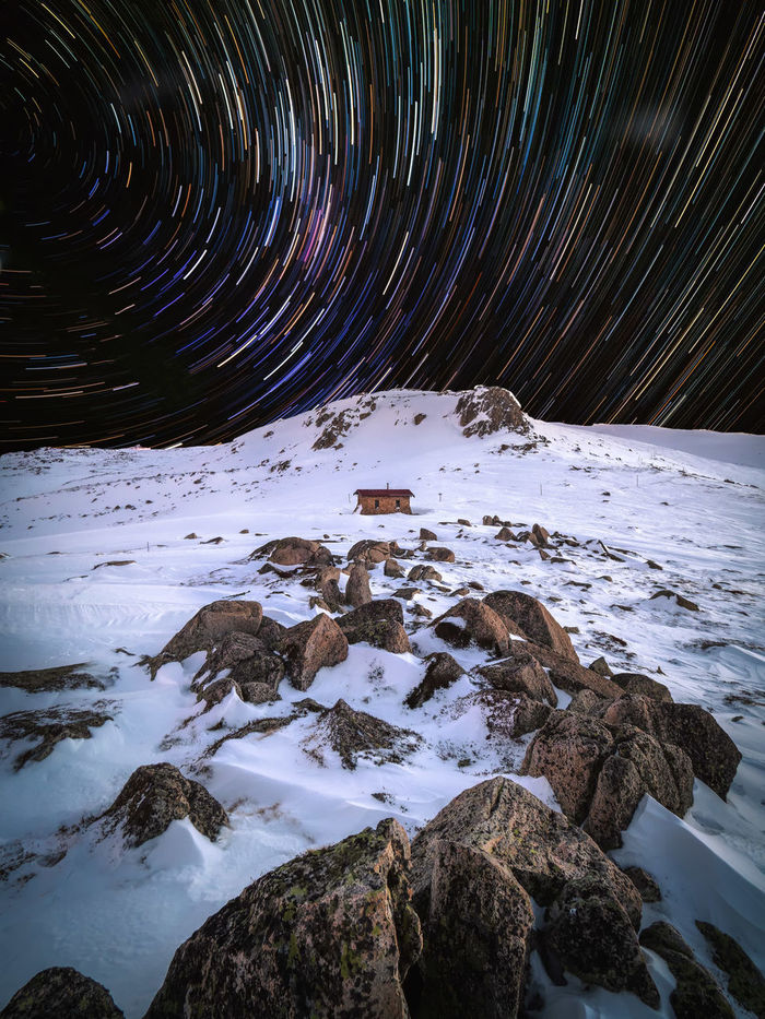 Star trails over snow covered landscape at night