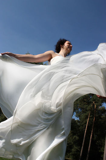 Beauty In Nature Blue Bride Dancing Day Happy Joy Of Life Low Angle View Nature One Person Outdoors People Real People Sheet Sky Turning Around Wedding Dress White Female Peacock. Women Young Adult Young Women