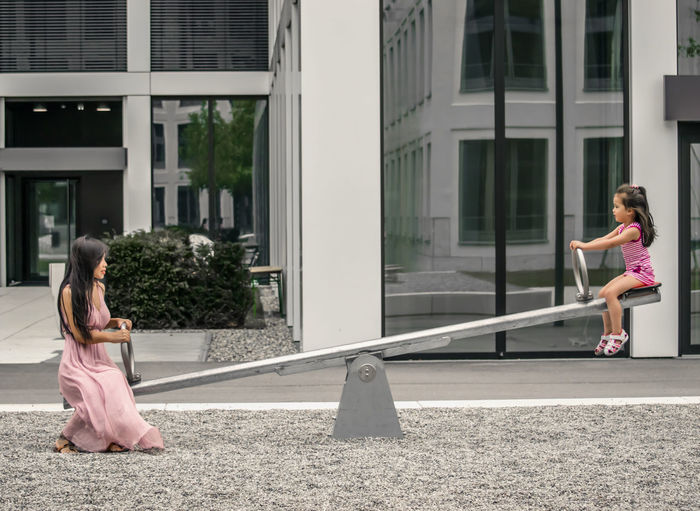 Side view of mother with daughter playing on seesaw against building