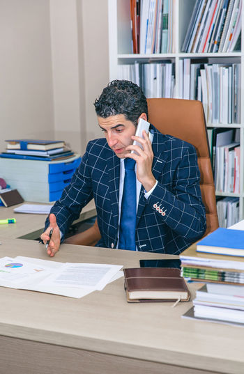 Serious businessman having a discussion by phone sitting in the office Business Busy Company Man Suit Working Business Finance And Industry Businessman Caucasian Chairman Chief Concentration Device Executive  Headquarters Jacket Job Male One Person Portrait Serious Smart Phone Sucess Technology Vertical