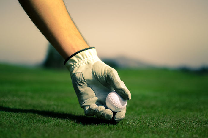 Hand with a glove is placing a tee with golf ball in the ground. Golf course with green grass with mountains in the background. Soft focus or shallow depth of field. Ball Close-up Club Golf Golf Golf Ball Golf Club Golf Course Golf Course Golfer Golfing Grass Grass Green Green Color Human Body Part One Person Outdoors Putting Green Slovenia Sport Sports Clothing Sportsman Stick Sunset