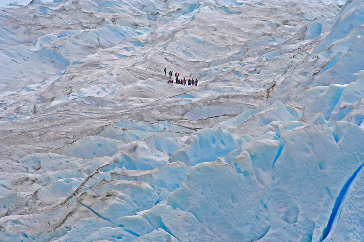 High angle view of people hiking on snow covered mountain