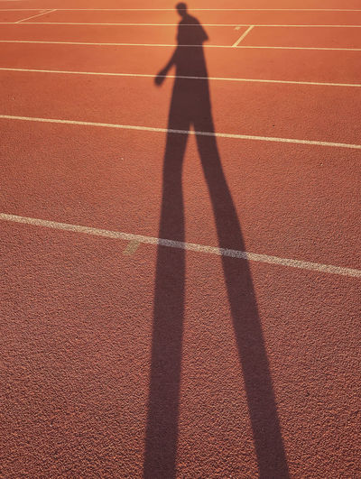 Shadow of man walking on running track