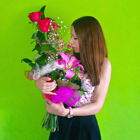 Beautiful young woman holding flower against green background