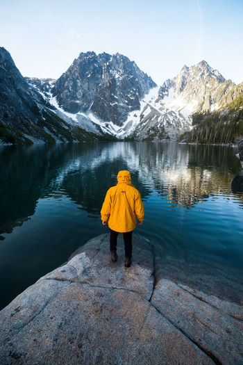 Rear view of person on lake by snowcapped mountain against sky