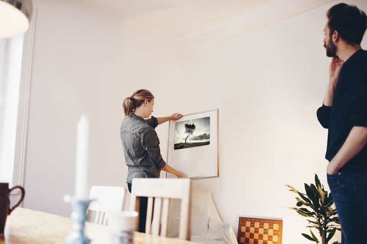 Young woman working on table against wall
