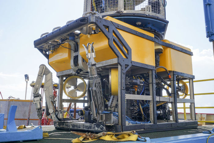 Oil and gas industrial. A commercial Remote Operated Vehicle (ROV) for deep sea survey purpose standby on the mini platform awaiting for launching to the sea. Competency Diving Droid Industrial Machinery Transportation Commercial, Deployment Exploration Hi-tech Hydraulic Engineering Inspection Maintenance Mechatronics Offshore Platform Oil And Gas Propeller Remote Operated Vehicle Robotics Safety Subsea Survey Technology, Underwater Vehicle