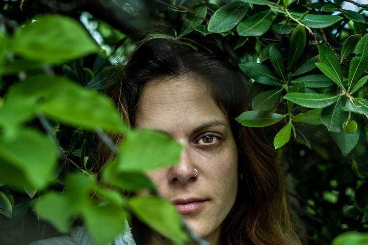 Close-up portrait of woman standing amidst plants