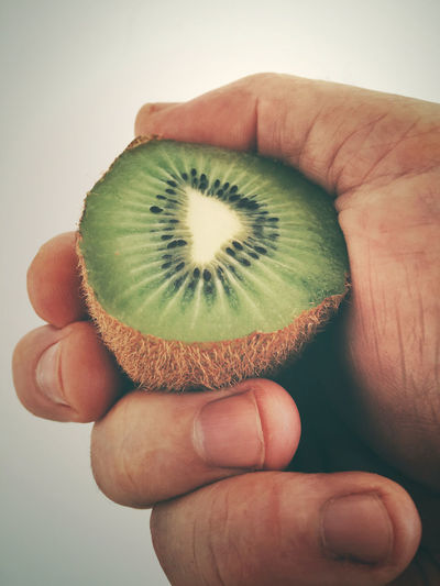 Close up of a skin on kiwifruit. Close-up Cook  Cooking Cropped Detail Focus On Foreground Food Fruit Green Color Health Healthy Healthy Eating Healthy Food Healthy Lifestyle Holding Human Finger Kiwi Kiwifruit Lifestyles Nature Part Of Person Personal Perspective Showing Unrecognizable Person