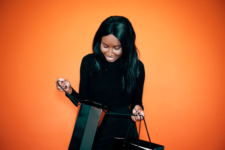 Smiling african american woman in total black looking inside the shopping bag against orange wall
