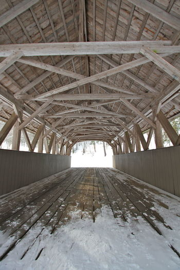 Winter Wood Wood Beams Architecture Bridge - Man Made Structure Brown Built Structure Connection Covered Bridge Covered Bridges Of New Hampshire Day Diminishing Perspective Franconia Notch Girder Gray Indoors  New Hampshire No People Roof Beam Snow Underneath vanishing point