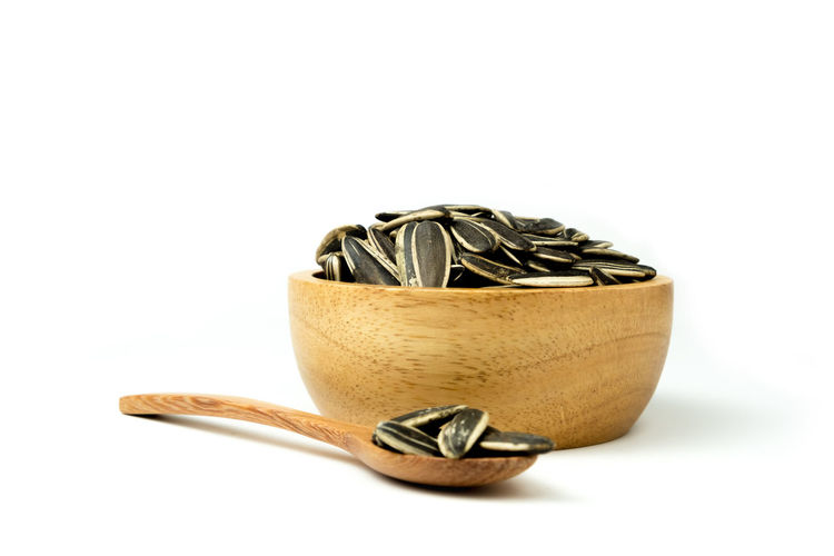 Close up of sunflower seeds isolated in wooden bowl against and spoon on white background and clipping path. Sunflower Seeds White Background Isolated Food Organic Agriculture Snack Ingredient Shell Pile Healthy Diet Tasty Nutrition Dry Roasted Close-up Objects Vegetarian Heap Clipping Path Cereal Bowl Wooden