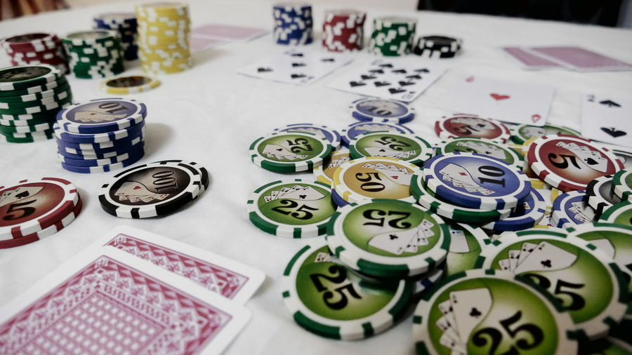 Close-Up Of Gambling Chips And Playing Cards On Table