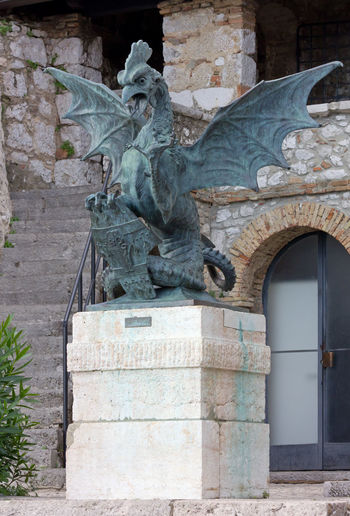 Statue against old building
