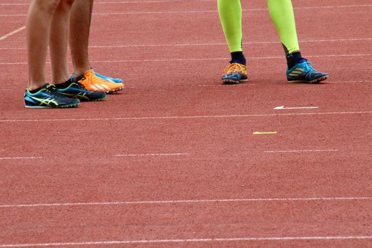 Low section of athletes standing on running track