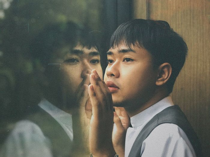 Close-up of young man looking through window