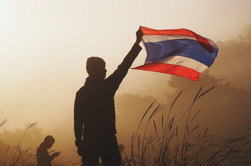 Rear view of man holding thai flag against sky during sunset