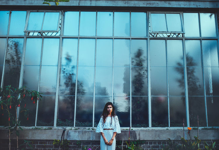 greenhouse. One Person Real People Young Adult Young Women Lifestyles Architecture Front View Standing Leisure Activity Portrait Casual Clothing Built Structure Women Looking At Camera Building Exterior Day Adult Window Outdoors Hairstyle Beautiful Woman