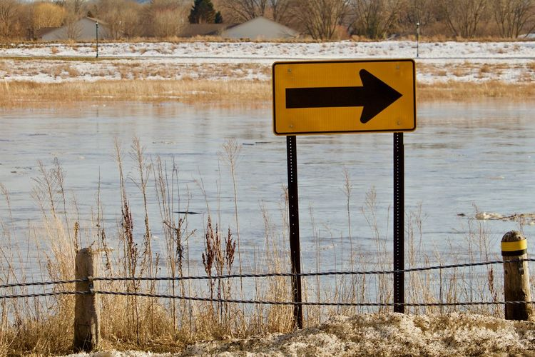 Road sign by lake during winter
