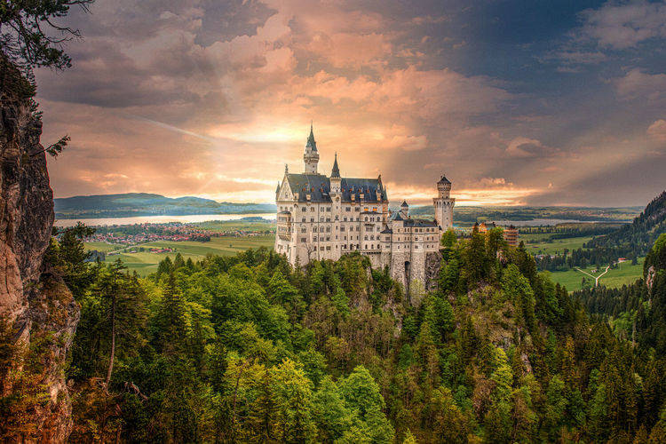 Neuschwanstein Castle Sky Cloud - Sky Tree Building Exterior Plant Built Structure Architecture Building Beauty In Nature Nature Mountain Scenics - Nature Sunset Belief Outdoors No People Religion Castle Neuschwanstein Castle
