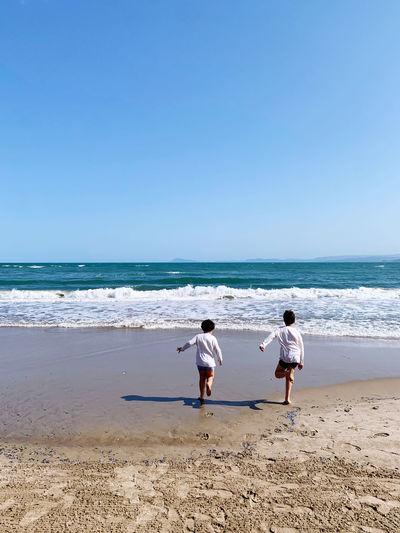 Rear view of boys on beach against clear sky