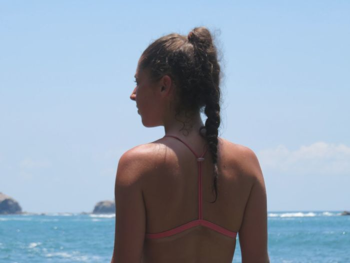 Rear view of young in bikini woman looking at sea against sky
