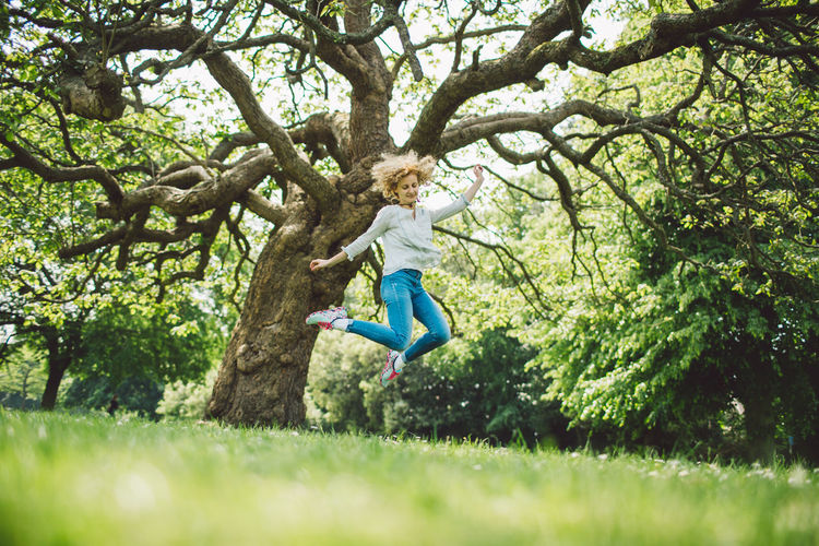 Full Length Of Mid Adult Woman Jumping Against Tree In Field