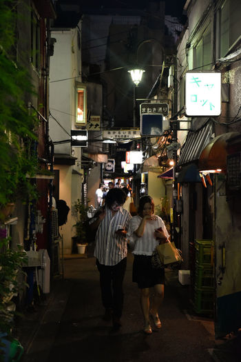 Golden Gai Adult Architecture Building Exterior Built Structure Casual Clothing City City Life Full Length Illuminated Leisure Activity Lifestyles Men Night Outdoors People Real People Rear View Standing Street The Way Forward Togetherness Two People Walking Women