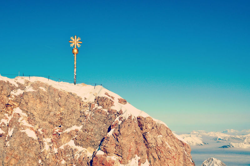 Summit cross on zugspitze mountain peak against clear sky