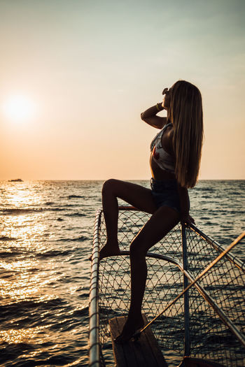 Water Sea Sky Sunset Beauty In Nature Real People Sitting Leisure Activity Lifestyles One Person Scenics - Nature Women Nature Adult Horizon Over Water Horizon Tranquil Scene Young Adult Outdoors Hairstyle