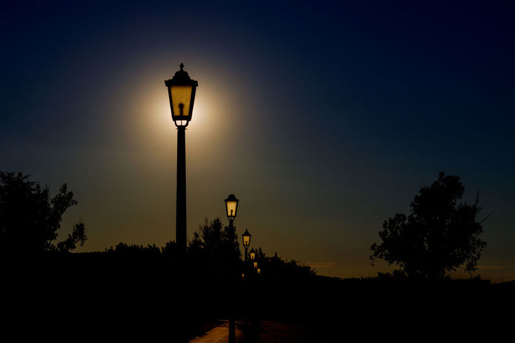 Silhouette street light against sky at sunset