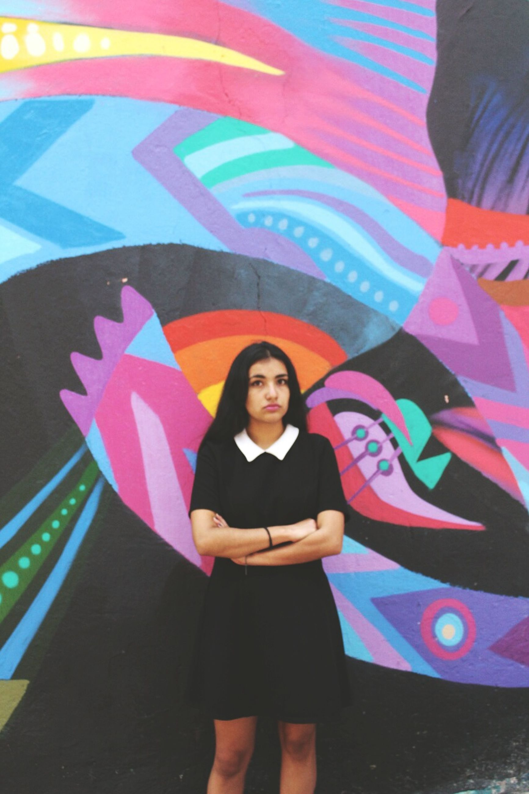 multi colored, one person, young adult, real people, front view, looking at camera, standing, graffiti, lifestyles, young women, beautiful woman, portrait, leisure activity, casual clothing, happiness, posing, outdoors, smiling, day, full length, people