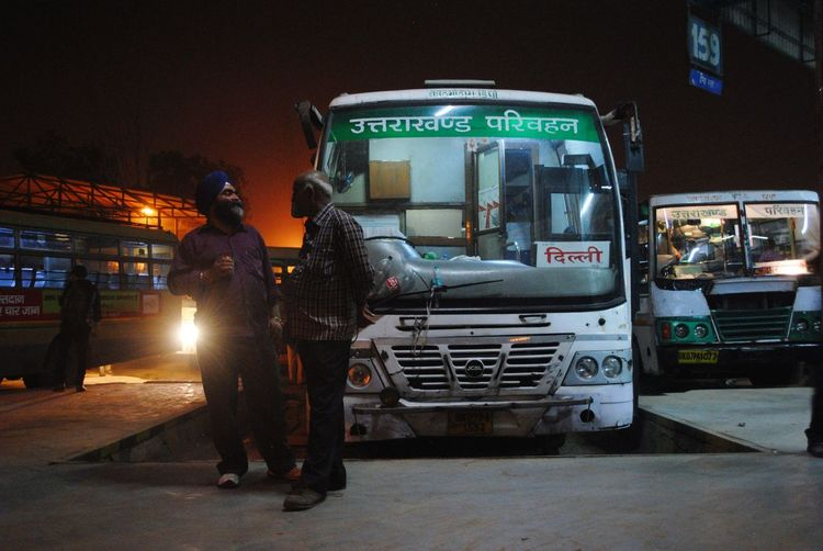 INDIA 2014 : The bus driver ( who wear Sikh turban) stand on platform with a man while talking together at Anand Vihar bus station. People Photography Lifestyle People Talking Locol Bus Transportation Terminal Night India Travel Photography Destination It's About The Journey