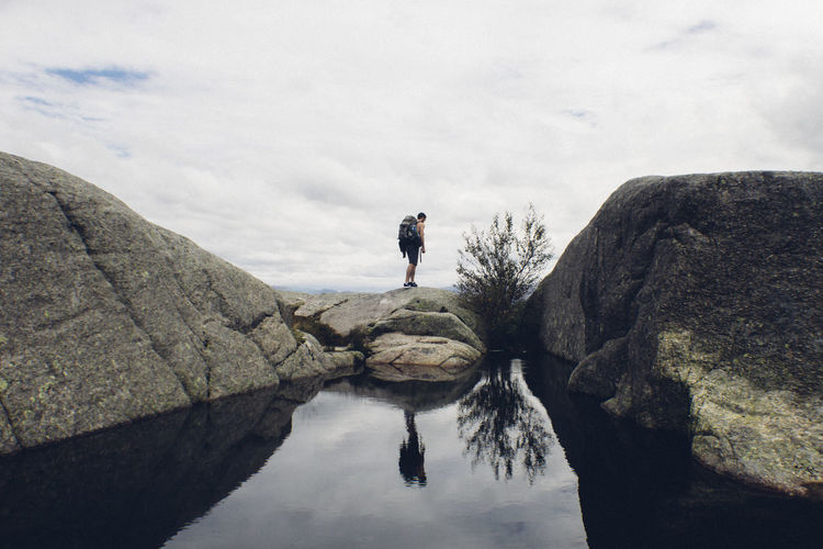 Rear view of hiker standing on rock by lake against cloudy sky