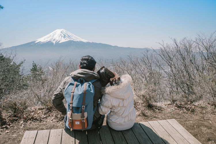 Rear View Of Woman Leaning On Man While Sitting On Observation Point Against Clear Sky