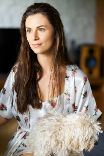 Close-up of woman with dog sitting at home