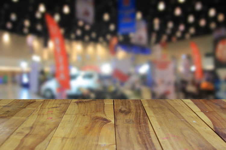 Wooden table and blurred image of motor show,show room,motor expo for background Abstract; Acceleration; Aerial; Auto; Automobile; Automotive; Background; Benz; Blur; Blurred; Bokeh; Business; Car; Color; Concept; Cooper; Crowd; Defocused; Depth; Distribution; Dream; Drive; Exhibition; Exterior; Inside; Interior; Lifestyle; Light; Min Close-up Day Focus On Foreground Indoors  No People Stadium Table Wood - Material
