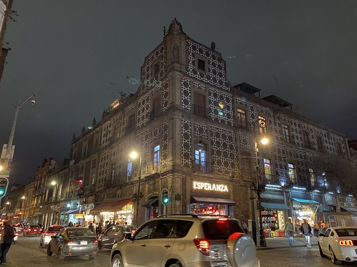Traffic on city street by buildings against sky at night