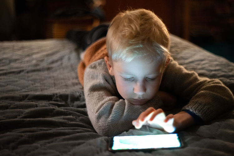 Addiction Bed Bedroom Child Childhood Cozy Digital Tablet Domestic Room Front View Furniture Headshot Indoors  Innocence Looking Lying Down Lying On Front Offspring One Person Real People Relaxation Technology Wireless Technology